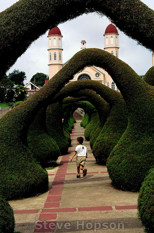 A young boy runs through a topiary maze at Iglesia de San Rafael in Zarcero, Costa Rica, June 2003. Evangelisto Blanco created the topiary maze in Parque Francisco Alvarado in the 1960s. Shrubs in the maze are trimmed into animals and abstractions. Zarcero is the capital city of canton Alfaro Ruiz in the province Alajuela in Costa Rica. Zarcero, known for its brisk mountain climate, is a dairy and agricultural area noted for organic farming enterprises.