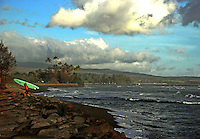 Hawaii, South Pacific. Stormy day in April. A surfer carries his surfboard from the beach under a lowering sky.