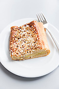 Danish pastry on a white plate with fork - traditional sweet cake with apple nuts and sugar as typical specialty snack in Denmark