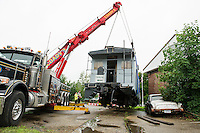 John Dapergolas of John's and John Kemp of Coady's operate the control panels to maneuver Pitman's Freight Room's caboose as they move it onto its new set of tracks Wednesday afternoon.  (Karen Bobotas/for the Laconia Daily Sun)