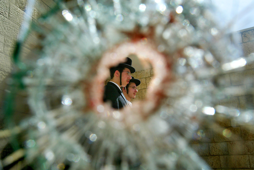 Ultra-Orthodox Jews are seen through a door damaged by bullets at a Jewish religious school in Jerusalem March 7, 2008. A Palestinian gunman shot dead at least eight people at a Jewish religious school in Jerusalem, but Israel said the killings would not derail U.S.-sponsored peace talks. Photo by Olivier Fitoussi