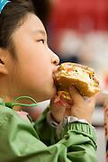 Girl eating a hamburger at Burger King.