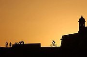 "SAN JUAN, PUERTO RICO  - 6.27.02 -  EL MORRO - At Fuerte San Felipe del Morro, affectionately known as ""El Morro"", sanjuaneros bask in the sunset on June 19, 2002 while mountain bikers take advantage of the open public space surrounding the colonial fort in Old San Juan to complete their workout. El Morro, a six-level fortress dates to 1539 and may be the oldest Spanish fort in the Americas. Due to the lack of open public space in Puerto Rico, joggers and mountain bikers can be often spotted working out in parking lots and in open, accessible areas like El Morro.  cq names    DIGITAL PHOTO BY PATRICK RAYCRAFT/THE HARTFORD COURANT"