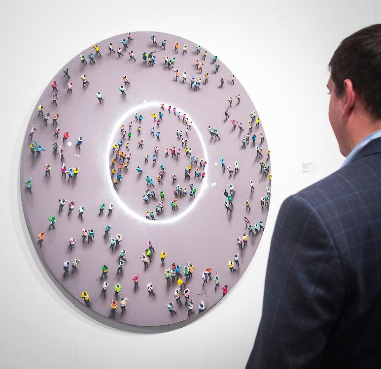 Man srudies Concéntrico by Juan Genovés at Art Basel Miami 2012.
