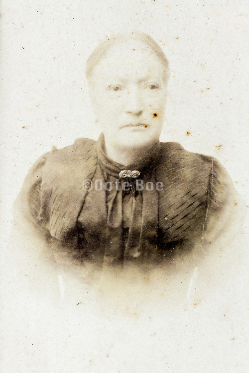 fading and damaged 1900s portrait of adult woman