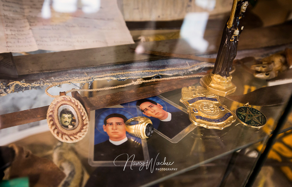 A case at the U.S. Border Patrol headquarters in Tucson, Ariz., displays items agents collected from people apprehended for unlawful entry. Holy cards featuring St. Toribio Romo, a popular patron of Mexican migrants, sit among knives, fake Border Patrol badges and clothing, water jugs, canned food and other items. NANCY WIECHEC
