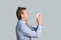 Side view of young man sneezing while trying to cover mouth over colored background