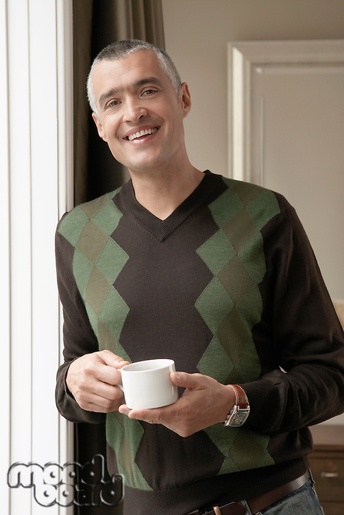 Smiling man with cup of coffee (portrait)