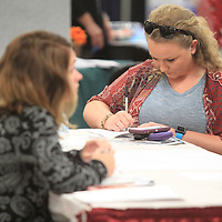 Katie Denton, of Ecru, fills out an application at the Excelsior Staffing booth, as she searches fo a job Tuesday at the Mega Job Fair that was held in Building V of the Tupelo Furniture Market. Excelsior Staffing hires for specific manufacturing companies arcoss the region.