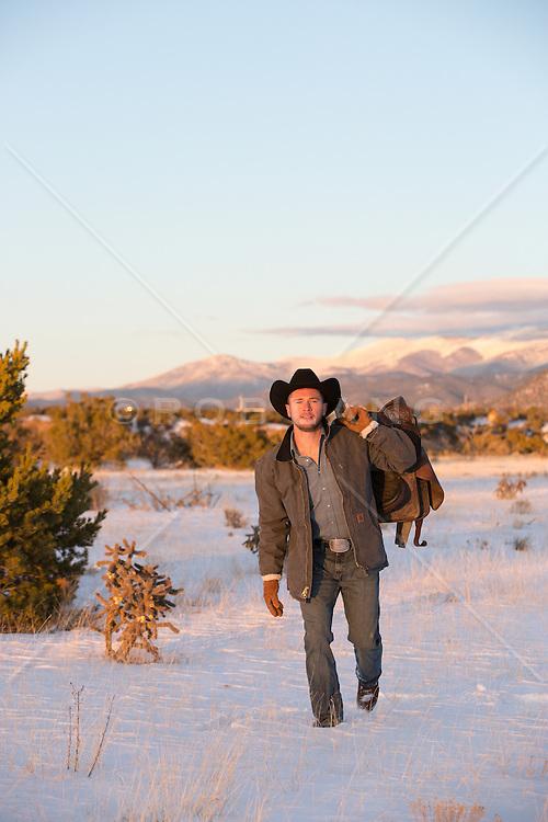 cowboy with a saddle walking through snowy mountain top