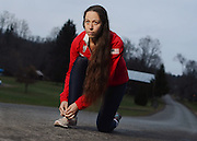 Erin Taylor-Talcott is a racewalker who has qualified for the men's Olympic trials in January in the 50-kilometer (31 mile) event. Taylor-Talcott ties her shoes in front of her home in Owego, N.Y., Tuesday, Nov. 15, 2011..(Heather Ainsworth for The New York Times)