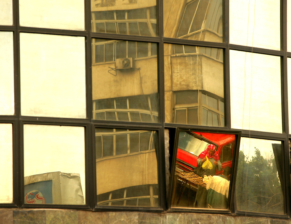 A car and a woman is reflected in a window in the Shubra area of Cairo, Egypt. Photo by Wally Nell