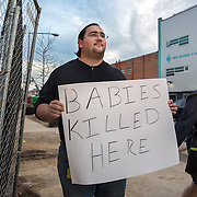 WASHINGTON, DC - MAR10: Robert Weiler Jr., 35, a fervent anti-abortion protester, holds a sign outside the construction site of the new Planned Parenthood which  is adjacent to the Two Rivers Public Charter School, March 10, 2016, in Washington, DC, as parents walk by to pick up their children from school The Two Rivers school is suing Weiler to prevent him from protesting outside the Planned Parenthood because it so close to the school.<br /> <br /> Weiler served five years in federal prison for planning to bomb another clinic. In 2006, authorities received information from Weiler&rsquo;s parents that they believed their son planned to destroy an abortion clinic. Weiler said he had intended to use a pipe bomb to blow up the abortion clinic in College Park. He also said he had planned tos hoot doctors who perform abortions. Since serving his prison sentence and probation, Weiler says he has protested at several places. (Photo by Evelyn Hockstein/For The Washington Post)
