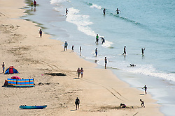 Holidaymakers enjoy the sunny weather on Crantock Beach in Newquay, Cornwall.