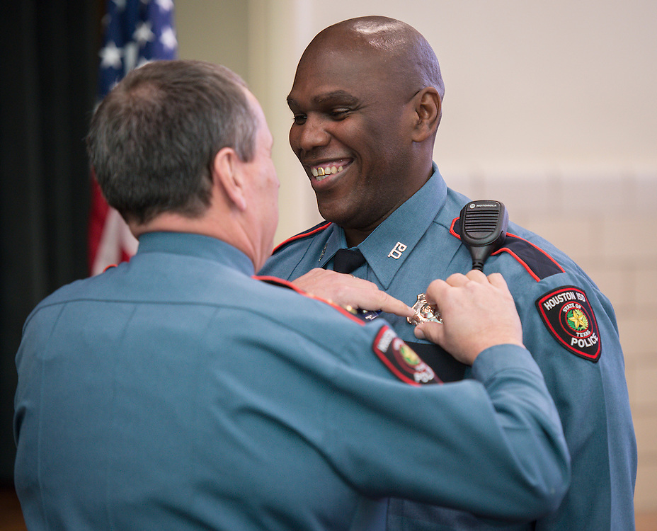 James Wilmore, right, receives his badge from Chief Mock during a swearing-in ceremony for new officers at the Houston ISD Police Department, March 3, 2014.