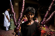 A young boy is moving bundles of just painted glass bracelets inside a house transformed into a small-scale workshop in the slum surrounding Firozabad, renowned as the 'glass city', in Uttar Pradesh, northern India. Due to extreme poverty, over 20.000 young children are employed to complete the bracelets produced in the industrial units. This area is considered to be one of the highest concentrations of child labour on the planet. Forced to work to support their disadvantaged families, children as young as five are paid between 30-40 Indian Rupees (approx. 0.50 EUR) for eight or more hours of work daily. Most of these children are not able to receive an education and are easily prey of the labour-poverty cycle which has already enslaved their families to a life of exploitation. Children have to sit in crouched positions, use solvents, glues, kerosene and various other dangerous materials while breathing toxic fumes and spending most time of the day in dark, harmful environments. As for India's Child Labour Act of 1986, children under 14 are banned from working in industries deemed 'hazardous' but the rules are widely flouted, and prosecutions, when they happen at all, get bogged down in courts for lengthy periods. A ban on child labour without creating alternative opportunities for the local population is the central problem to the Indian Government's approach to the social issue affecting over 50 million children nationwide.