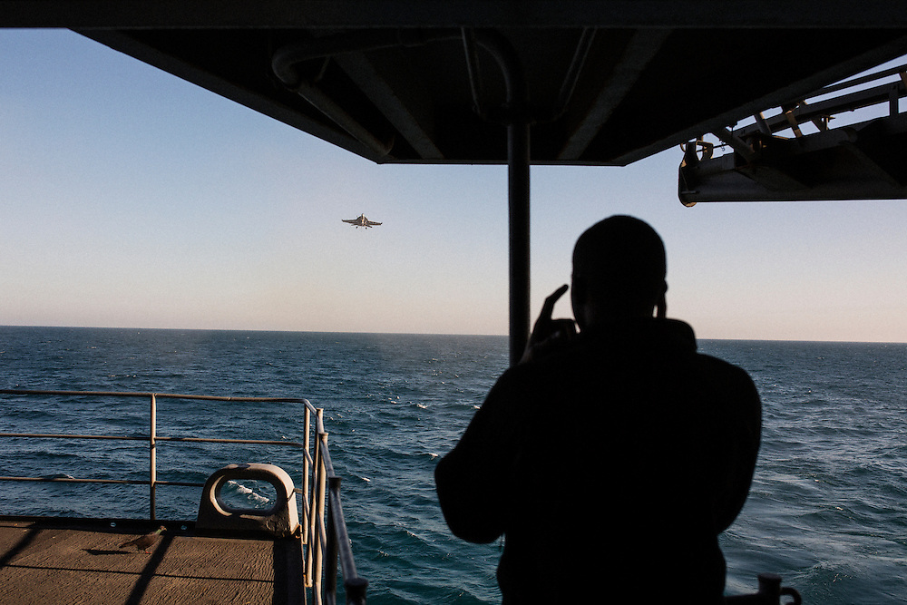 A crew member watches as a F/A-18 Hornet prepares to land from the fantail (the rear of the ship), just below the flight deck<br /> <br /> Aboard the USS Harry S. Truman operating in the Persian Gulf. February 25, 2016.<br /> <br /> Matt Lutton / Boreal Collective for Mashable