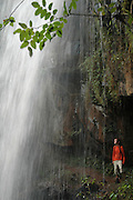 A tourist stands underneath the waterfall in Livingstonia..Livingstonia, Malawi, Africa.© Demelza Cloke