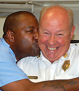 staff photo by Phil Grout..As Capt. Bragg's retirement nears, he finds he has to endure the.good natured kidding from his station friends like Darnell Harrison.has plants an impromptu kiss on his captain.