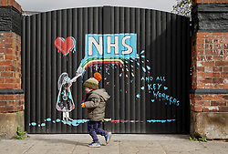 © Licensed to London News Pictures. 03/04/20. Pontefract, UK. A boy runs past a new mural by local artist Rachel List painted in support of the NHS near the Hope and Anchor pub in Pontefract, West Yorkshire. Photo credit: Scott Merrylees/LNP