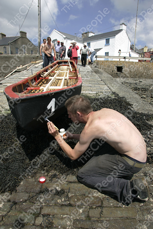 Kieran Clancy From Kilkee Co.Clare painting on the Number on the Currachs before the Start of the Currachs Racing in Cappa Co.Clare.<br />