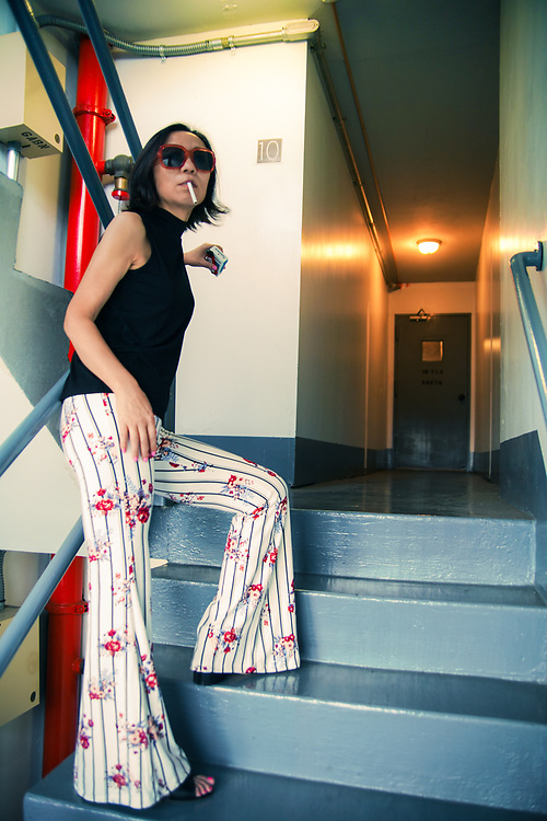 Portrait of cute stylish Asian girl smoking cigarette in stairwell.