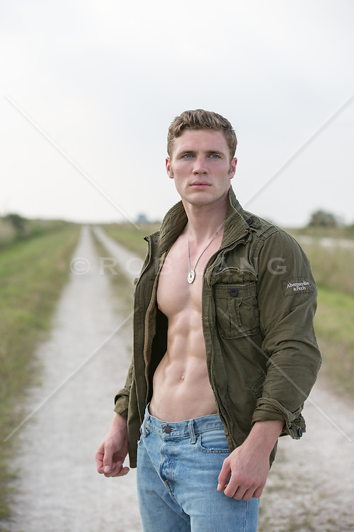 good looking All American man with an open jacket and no shirt on a dirt road