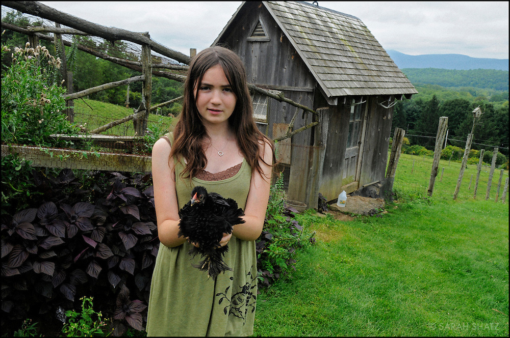Girl with chicken on a farm