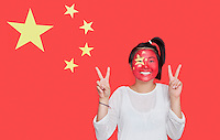 Portrait of young Asian woman with painted face gesturing peace sign against Chinese flag