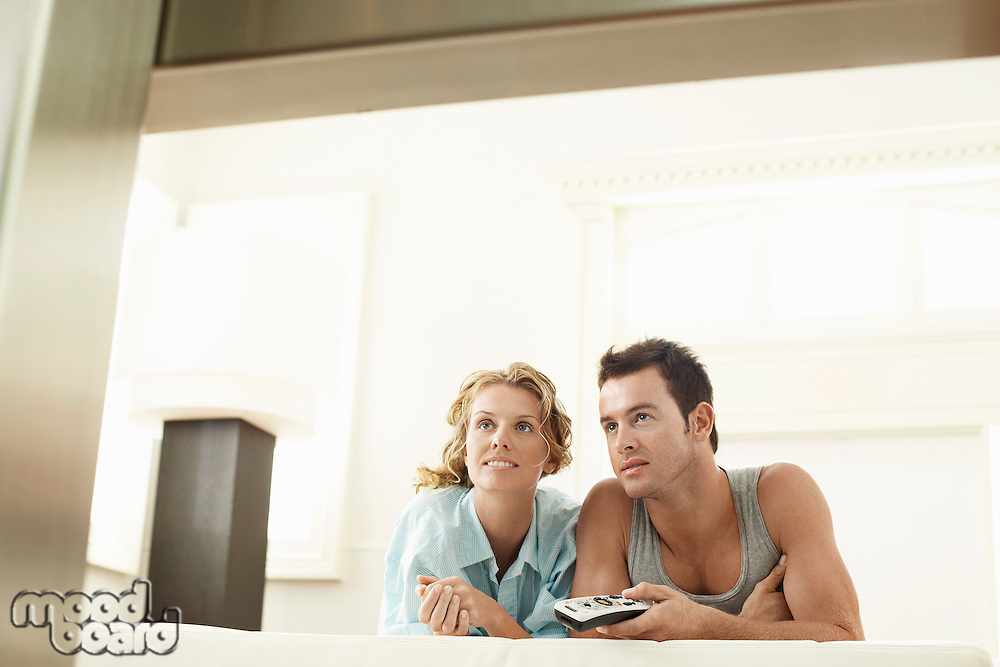 Couple lying on bed together man holding remote control