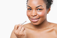 Portrait of African American young woman applying lip gloss with brush over white background