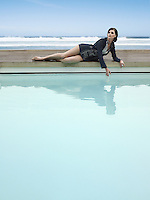 Woman reclining by outdoor pool by ocean
