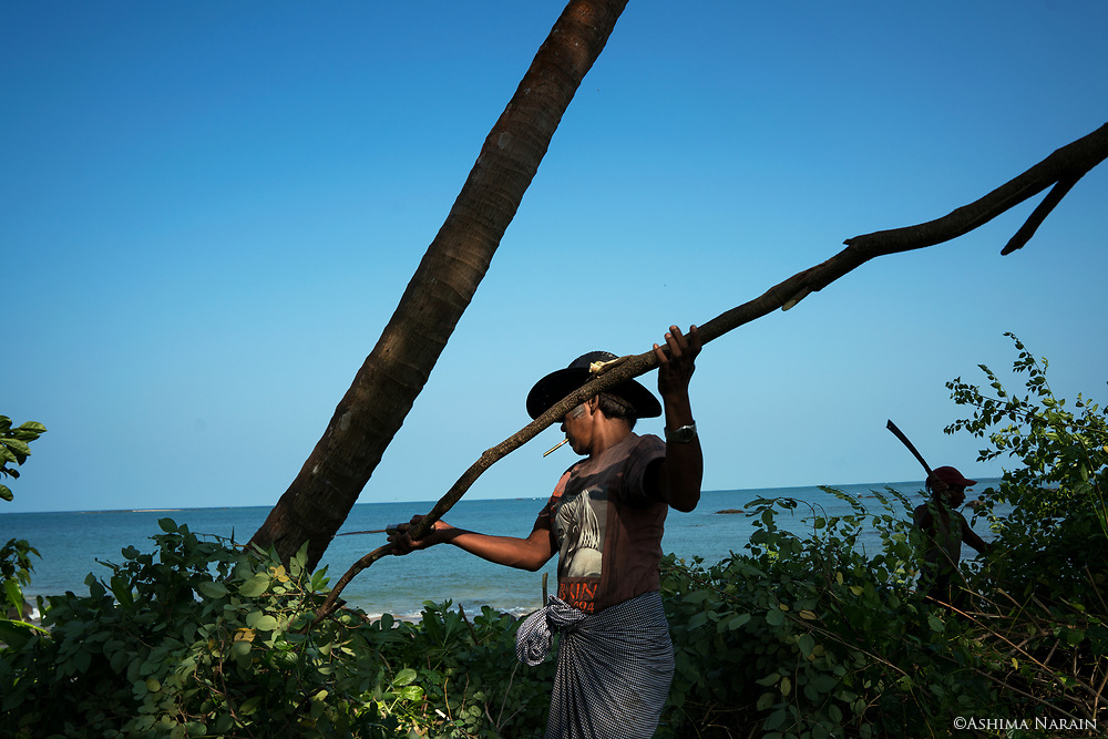 U Nyo Kyi (in the hat) and Ko Naing Win cut down some wild trees outside the WIF Guesthouse to ensure that if the navy pass, the view from the sea to the land is not obstructed. <br />