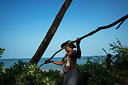 U Nyo Kyi (in the hat) and Ko Naing Win cut down some wild trees outside the WIF Guesthouse to ensure that if the navy pass, the view from the sea to the land is not obstructed. <br /> U Nyo Kyi is the guesthouse manager, and Ko Naing Win is a crab catcher and a daily wager.