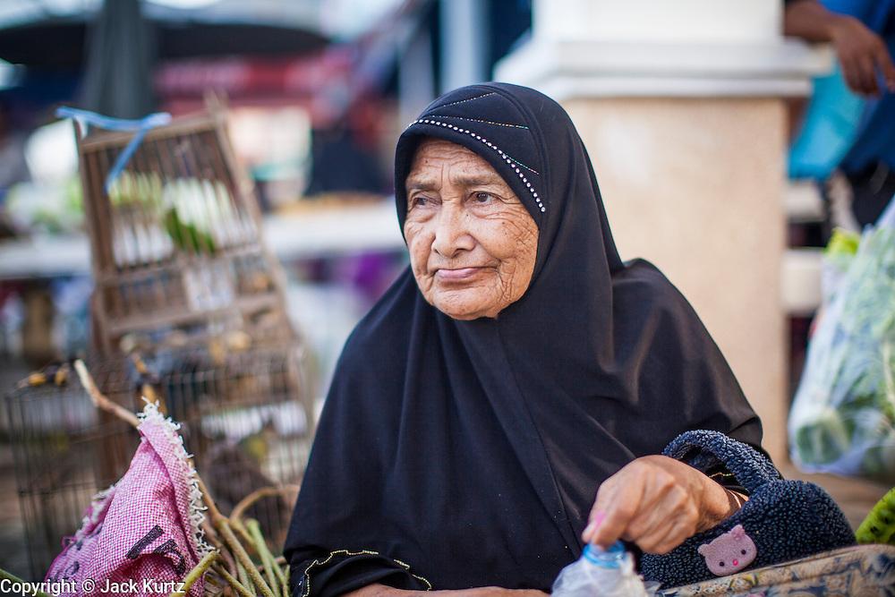 25 OCTOBER 2012 - PATTANI, PATTANI, THAILAND: A woman vendor in the market in Pattani, Thailand.      PHOTO BY JACK KURTZ