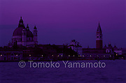 Santa Maria della Salute and the Campanile of St. Mark's Basilica are seen across the canal of  Giudecca at dusk.  Romantic view of Venice with lights along close to the water and the buildings against a purple colored sky and water, The Salute church and St. Mark's bell tower are dimly lit at dusk.