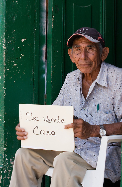 "An elderly man sits in his doorway attempting to sell his house to passers by. He is holding a sign that sez""house for sale""The economy of Nicaragua is currently in turmoil. Granada is Nicaragua's most famous city. founded in 1524 it is one of best examples of Spanish colonial architecture in the Americas. .it has a varied history including its almost total destruction by filibuster William Walker in a childlike tantrum. Today it is a popular tourist town though retains a strong sense of its own identity."