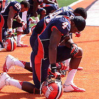 Illinois football players kneel before the start of the game at Memorial Stadium against Charleston Southern.