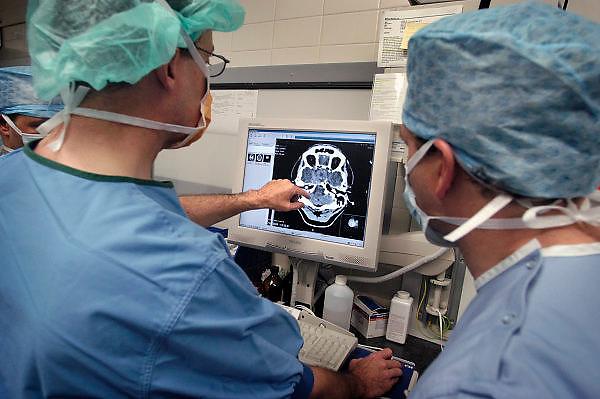 Nederland, Nijmegen, 3-5-2005..Voor de hersenoperatie bekijkt de chirurg, hersenchirurg, met zijn assistenten een scan van het gebied waar een tumor in de hersenen, het hoofd, verwijdert gaat worden...Geneeskunde, kanker, operatie, operatietechniek, gezondheidszorg, zorgverzekeraar, ziekenhuis, specialist..basisverzekering, ziektekostenverzekering...Foto: Flip Franssen