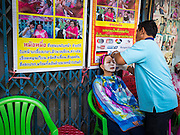 "17 FEBRUARY 2015 - BANGKOK, THAILAND: A man works on a client at a threading stand on Charoen Krung Road in Bangkok's Chinatown. About a dozen people, mostly women, have set up shop on the sidewalk to do hair removal for clients. They use thread to remove hair, a practice called ""threading"" which originated in India more than 6,000 years ago. It's growing in popularity in the US and Europe as an alternative to waxing. A cotton or polyester thread is pulled along unwanted hair in a twisting motion, the hair is trapped in a mini lasso, and lifted out of the follicle.    PHOTO BY JACK KURTZ"