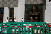 Construction fencing and the luxury shop window of Louis Vuitton featuring their exclusive range of bags with the face of Leonardo da Vinci's Mona Lisa - a collaboration with the artist Jeff Koons and part of work entitled The Masters Collection, on 5th July 2017, on New Bond Street, in London England.