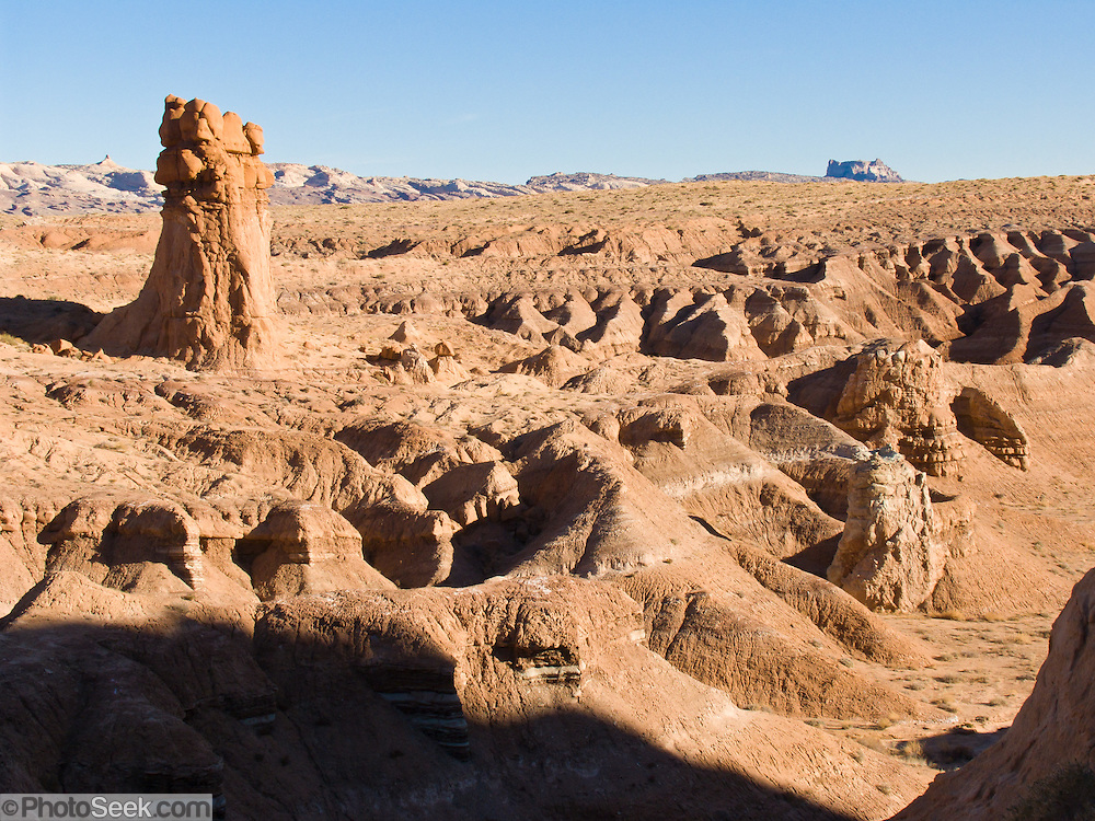 Admire fanciful hoodoos, badlands, mushroom shapes, and rock pinnacles in Goblin Valley State Park, in Emery County between the towns of Green River and Hanksville, in central Utah, USA. The Goblin rocks eroded from Entrada Sandstone, which is comprised of alternating layers of sandstone (cross-bedded by former tides), siltstone, and shale debris which were eroded from former highlands and redeposited in beds on a former tidal flat.
