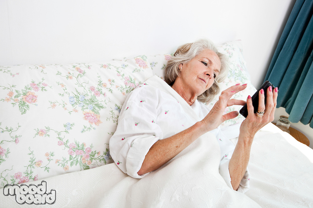 High angle view of senior woman using smart phone in bed at home