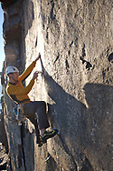 Rock climber in Maine sets a protection on a granite wall in Arcadia National Park Maine
