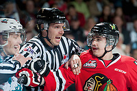 KELOWNA, CANADA - MAY 1: Linesman Ryan Gibbons gets between Justin Kirkland #23 of Kelowna Rockets and Blake Heinrich #16 of Portland Winterhawks during the second period of game 5 of the Western Conference Final on May 1, 2015 at Prospera Place in Kelowna, British Columbia, Canada.  (Photo by Marissa Baecker/Getty Images)  *** Local Caption *** Ryan Gibbons; Blake Heinrich; Justin Kirkland;
