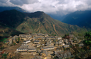 An wide aerial landscape of Ghandruk (also Gandruk), a town and Village in Kaski District in the Gandaki Zone of northern-central Nepal. At the time of the 1991 Nepal census it had a population of 4,748 persons living in 1,013 individual households. Situated in what is known as the Annapurna Sanctuary (conservation region), a 55-km-long massif whose highest point, Annapurna I, stands at 8,091 m (26,538 ft), making it the 10th-highest summit in the world. The village is also a stopping-off point for trekkers and backpackers who pass-by on their way to the walk in high peaks. The Mountain Region (Parbat in Nepali) is situated at 4,000 meters or more above sea level. Houses and dwellings are substantial structures with properties well-swept and well-maintained.