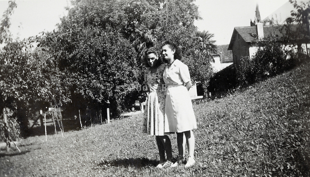 two woman in a grass field behind houses