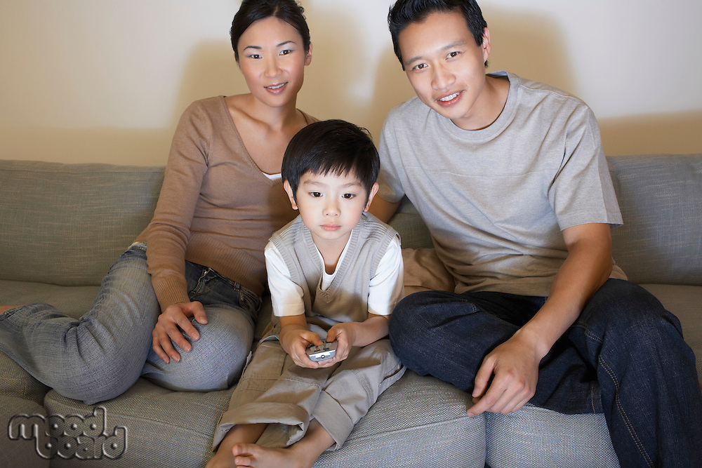 Couple sitting on sofa Watching Television while son is using remote control