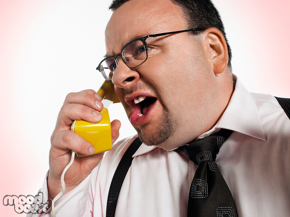 Businessman yelling into phone close-up