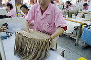 A woman inspects the quality of a batch of beige bras in the Top Form factory in Longnan, China.